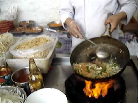 Chinese wok cooking - stir fried chicken with noodles